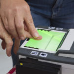 Man guiding another in using a fingerprint scanner