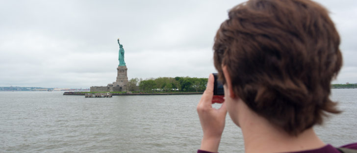 Young woman taking a photo of the Statue of Liberty