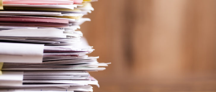 Large stack of files, paperwork. Close-up. Desk, office. Nobody.