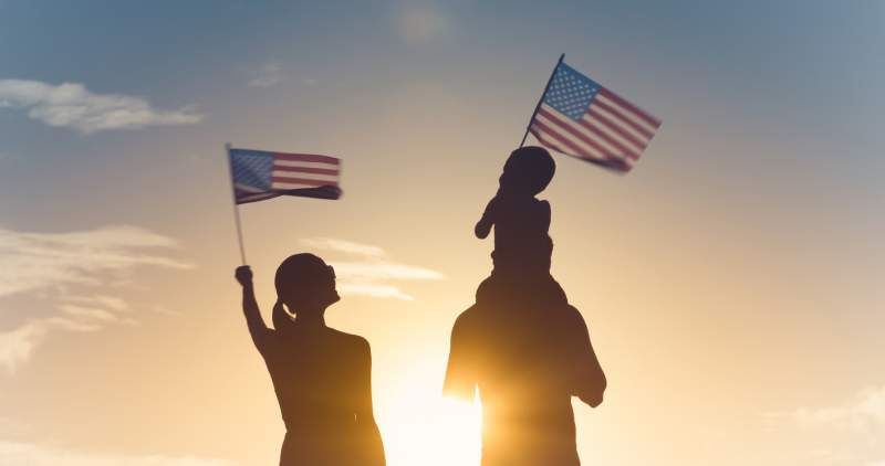 family celebrates nationalization with american flags